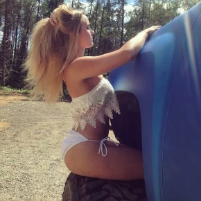 Blonde sitting on truck tire